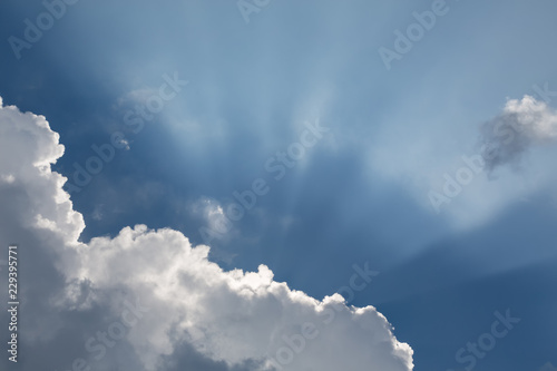 Fotografie, Obraz  Beautiful blue sky with sun rays emerging behind the clouds