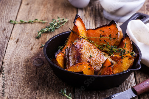 Fototapeta  Roasted chicken thighs with sliced butternut squash pumpkin and fresh thyme