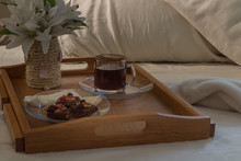 Stay Home And Enjoy Breakfast In Bed. Vegetarian Breakfast On A Sunday Morning. Vegan Brownies And Chai Tea On Wooden Tray. Stay In On A Sunny Winter Morning And Warm Your Hands Against The Hot Cup