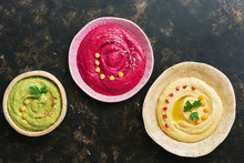 A Variety Of Colored Hummus, Classic Hummus, Beet Hummus, Hummus With Avocado On A Dark Rustic Background. Top View, Flat Lay. Clean Eating, Dieting, Vegetarian Party Food