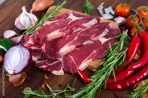 Fresh slices of beef with rosemary and vegetables assortment on wooden desk