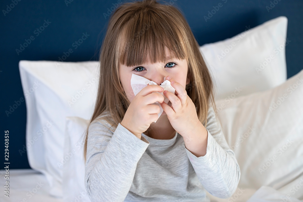Fototapeta cold sick child laying on bed and blowing her nose in tissue