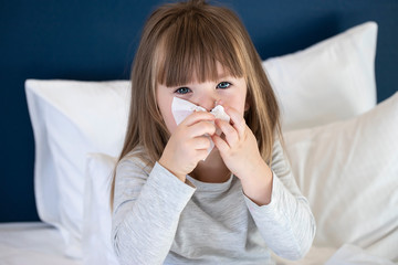 cold sick child laying on bed and blowing her nose in tissue