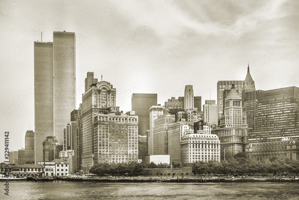 Fototapeta New York City skyline from NJ with World Trade Center featured as landmark of Twin Towers, destroyed in September 11, 2001. Sepia background, vintage style. Lower Manhattan in NYC, United States.