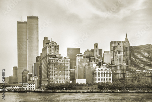 Photo Stands New York City New York City skyline from NJ with World Trade Center featured as landmark of Twin Towers, destroyed in September 11, 2001. Sepia background, vintage style. Lower Manhattan in NYC, United States.