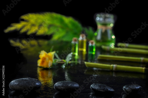 Poster Spa Beautiful spa composition with zen basalt stones and bamboo essential oil plants and flowers on black background