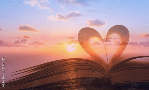 Fototapeta Heart shape from book against peaceful sunset. Reading, religion, love concept. Double exposure.  obraz