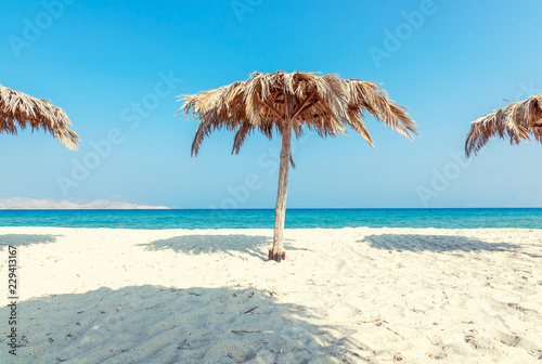 Beautiful landscape, tropical beach with white sand and umbrellas of palm leaves, calm down and travel, minimalistic concept