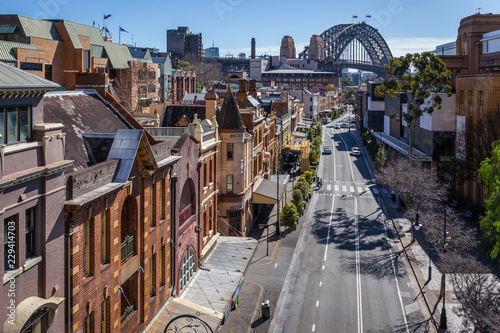 Foto auf Gartenposter Sydney View of George Street in the Rocks, the historic district of Sydney. In the background, the harbour Bridge.