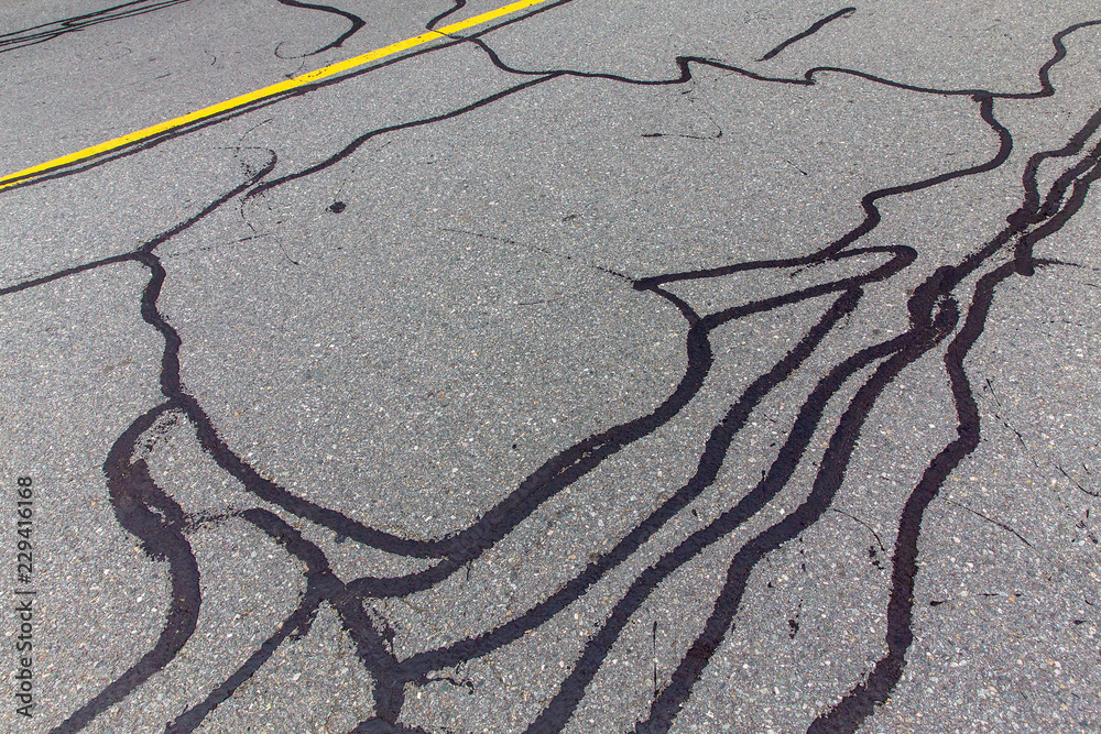 Fototapeta asphalt road with filled cracks. background of the fixed road