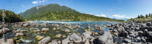 In de dag Khaki Panoramic landscape of the Petrohue River full of big stones with a forested little mountain chain