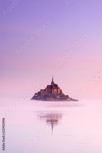 Canvas Prints Light pink old castle in foggy morning between sky and water in France