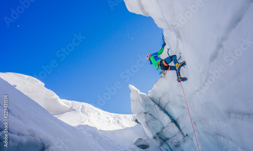 Fototapeta  Epic shot of an ice climber climbing on a wall of ice