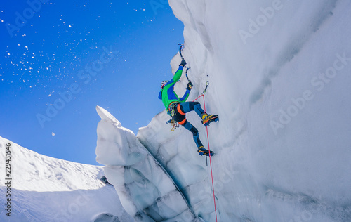 Obraz na plátne  Epic shot of an ice climber climbing on a wall of ice