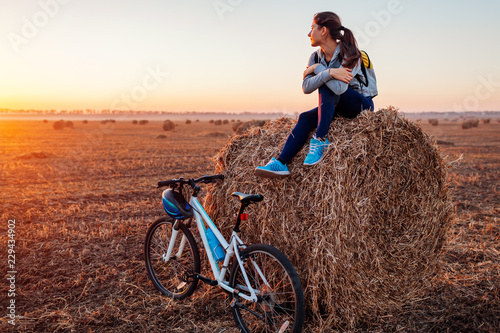 Young bicyclist having rest after a ride in autumn field at sunset. Woman admiring view sitting on haystack