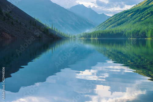 Keuken foto achterwand Bergen Ghostly mountain lake in highlands at early morning. Beautiful misty mountains reflected in calm clear water surface. Smoke of campfires. Amazing atmospheric foggy landscape of majestic nature.