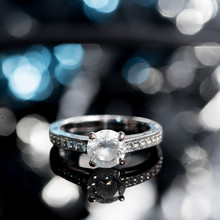 Engagement Ring With Diamond On Shiny Dark And Blue Background