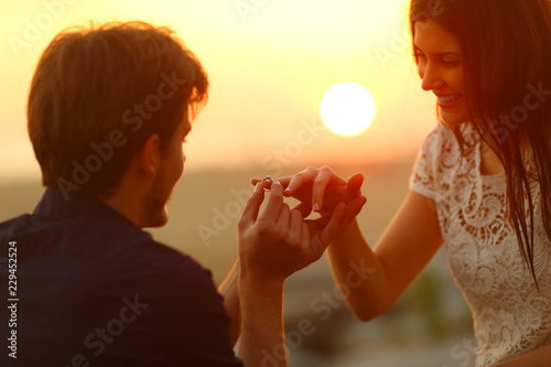 Man putting engagement ring in girlfriend finger
