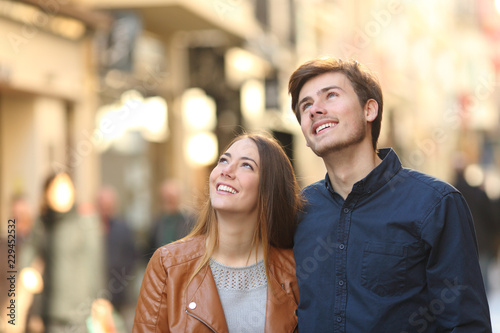 Couple walking and looking above in the street