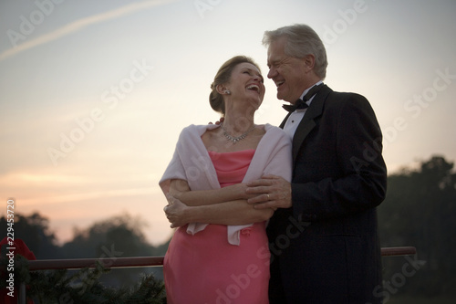 Mature adult couple dressed formally and dancing on a boat.