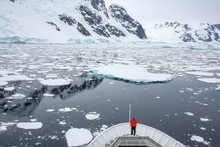 Person On Boat Looking At Icebergs And Mountains