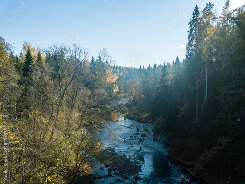 Tuinposter Groen blauw drone image. aerial view of wavy river in autumn colored forest