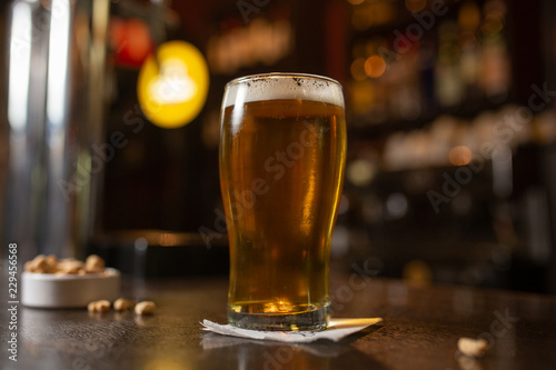 Photo Enjoy a pint glass of golden beer with snacks in a bar