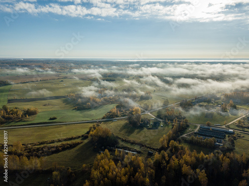drone image. aerial view of rural area with fields and forests covered in mist