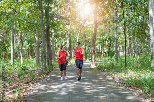 Happy senior asian woman with man or personal trainer jogging running in the park, Elderly care exercise sport activity concept