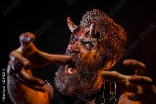 Photo  Halloween man demon hipster with horns stretch zombie hands