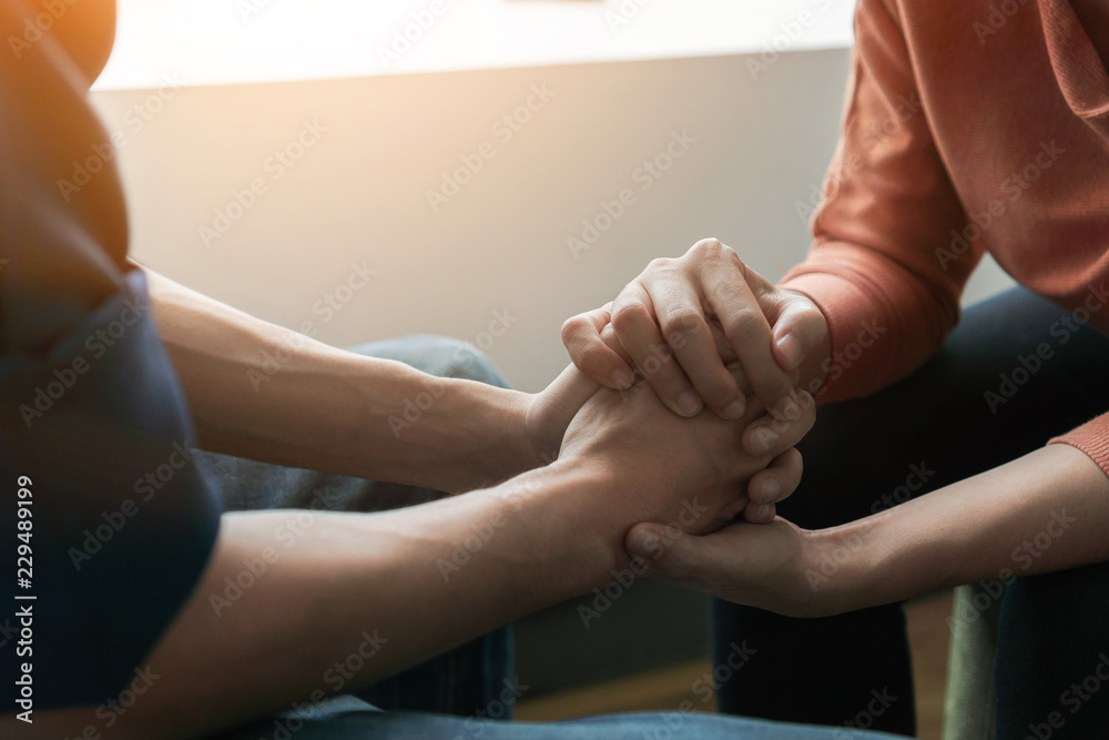 Fototapety, obrazy: PTSD Mental health concept, Psychologist sitting and touch hand young depressed asian man for encouragement near window with low light environment.Selective focus.