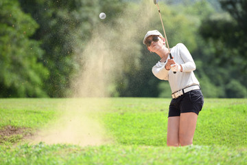 Fototapeta Asian woman golfer hitting a bunker shot