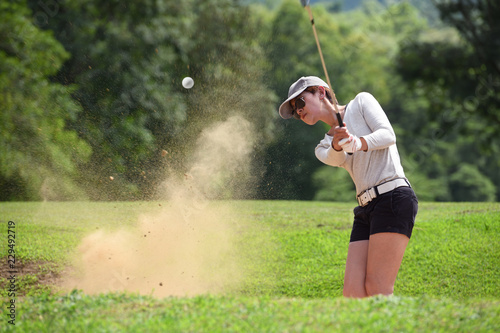 Deurstickers Golf Asian woman golfer hitting a bunker shot