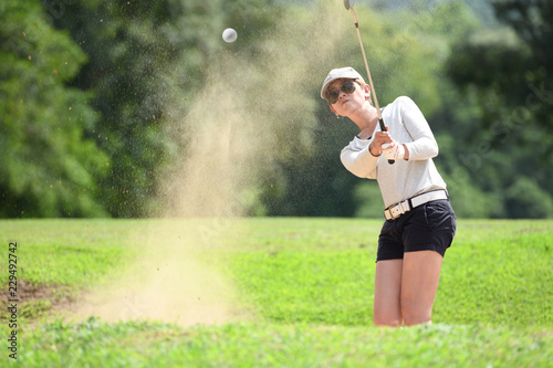 Asian woman golfer hitting a bunker shot