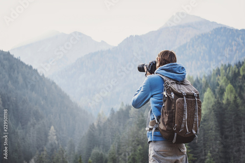 Fototapeta Young cheerful man photographer taking photographs with digital camera in a mountains