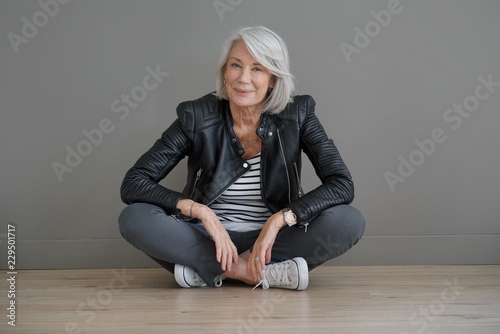Fotografía Modern senior woman sitting indoors with leather jacket
