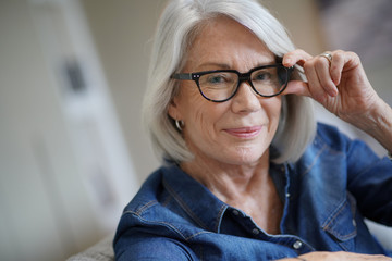 Fototapeta Attractive senior woman at home with eyeglasses
