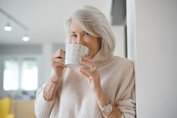 Fototapeta Senior woman at home with hot drink