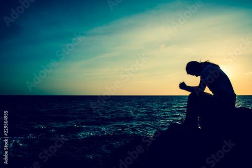 Fototapeta Silhouette women sitting alone on the rock