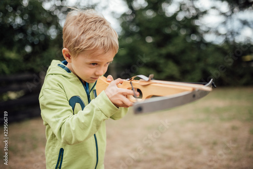 Photo Little boy shoots from a toy crossbow