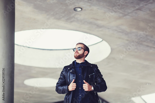 Papiers peints Arctique stylish man in a leather jacket and glasses posing on a gray background