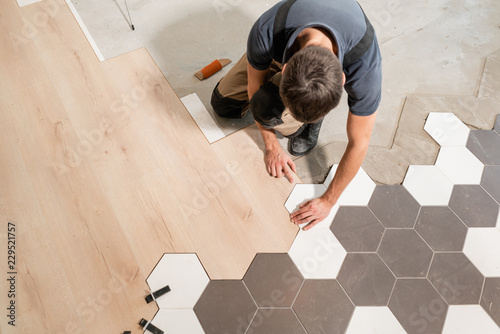 Fototapeta Male worker installing new wooden laminate flooring. The combination of wood panels of laminate and ceramic tiles in the form of honeycomb. Kitchen renovation. obraz