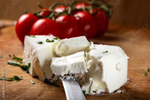 Pieces of white cheese on a wooden cutting board with cherry tomatoes