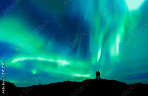 Deurstickers Noorderlicht Aurora borealis with silhouette love romantic couple on the mountain.Honeymoon travel concept