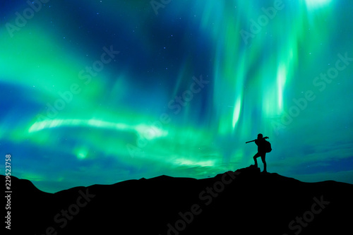 Photo sur Toile Aurore polaire Aurora borealis with silhouette standing photographer on the mountain.Freedom traveller journey concept