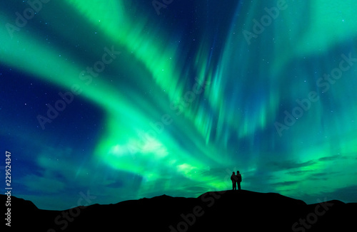 Poster Aurore polaire Aurora borealis with silhouette love romantic couple on the mountain.Honeymoon travel concept