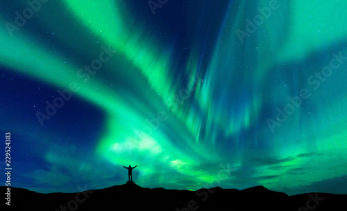 Fotografía Aurora borealis with silhouette standing man on the mountain