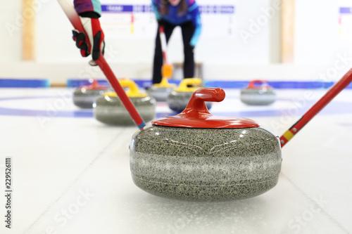 Foto Gra w curling. Zawodnik gra w curling na lodowisku