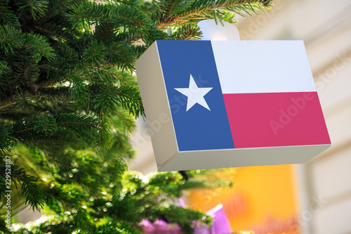 Foto op Plexiglas Texas Texas state flag printed on a Christmas gift box. Printed present box decorations on a Xmas tree branch on a street. Christmas shopping in United States, local market sale and deals concept.