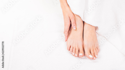 Poster Pedicure Female feet on towel. Nails getting a fresh and accurate look during a pedicure procedure